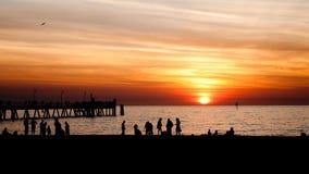 Mensen op het strand bij zonsondergang Stock Afbeeldingen
