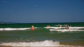 Mensen op het strand in de overzeese golven stock footage