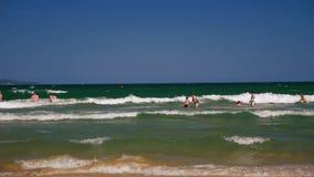 Mensen op het strand in de overzeese golven stock video