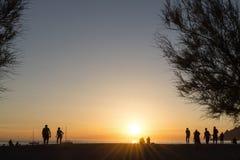 Mensen op het strand, die op de zonsondergang letten royalty-vrije stock afbeeldingen