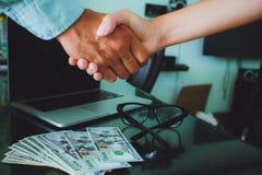 Mensen op het werk: man en vrouwenhand het schudden glazen, geld, overlapping Royalty-vrije Stock Foto's