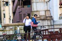 Mensen op hun cellphones in Japan stock afbeelding