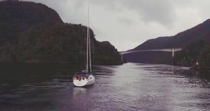 Mensen op jacht die langs fjord tussen heuvelige kusten varen stock video