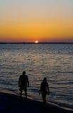 Mensen op Strand bij Zonsondergang stock foto