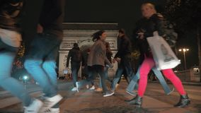 Mensen op zebrapad dichtbij Arc de Triomphe in nacht Parijs stock videobeelden