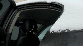 Mensen openingsdeur van auto Sneeuwdalingen binnen auto stock footage