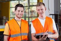 Mensen in oranje beschermend vest die bij fabriek werken stock foto