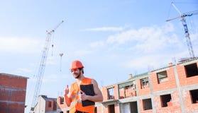 Mensen oranje vest en de helmwerken bij bouwwerf Contractantcontrole volgens plan Controlebouw stock afbeelding