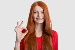 Mensen, overeenkomst en kinetisch gedragconcept De positieve rode haired vrouw met blije uitdrukking, toont o.k. teken met hand,  royalty-vrije stock foto's