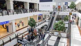 Mensen in roltrappen in een modern winkelcentrum Stock Afbeeldingen