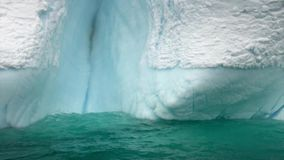 Mensen in rubberboot dichtbij Ijsijsschol en ijsberg van oceaanantarctica stock video