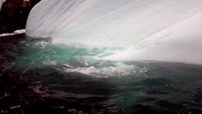 Mensen in rubberboot dichtbij Ijsijsschol en ijsberg van oceaanantarctica stock videobeelden