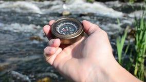 Mensen` s hand die een kompas op de achtergrond van een stormachtige rivier houden stock footage