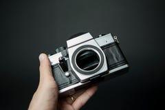 Mensen` s hand die een oude camera op een zwarte achtergrond houden Stock Afbeelding