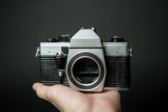 Mensen` s hand die een oude camera op een zwarte achtergrond houden Royalty-vrije Stock Foto