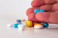 Mensen` s hand die een pil houden Talrijke kleurrijke drugs royalty-vrije stock afbeeldingen