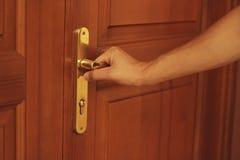 Mensen` s hand die houten deur openen Het houden van een gouden deurhandvat Royalty-vrije Stock Foto's