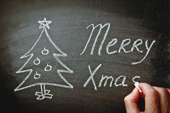 Mensen` s Hand die Vrolijke Kerstmis op Bord met Krijt schrijven Het Nieuwjaar van de krabbelkerstboom Royalty-vrije Stock Foto's