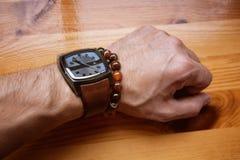 Mensen` s hand met een horloge en armbanddecoratie Royalty-vrije Stock Foto