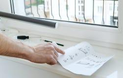 Mensen` s hand met instructie voor het installeren van blinde rol stock foto's