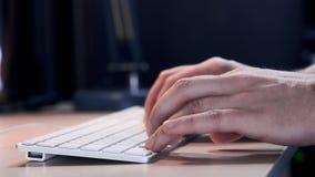 Mensen` s hand met slim horloge dicht omhooggaand type bij Desktoptoetsenbord in werkruimte De jonge zakenman werkt met genoegen stock video
