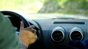 Mensen` s hand op het stuurwiel die een auto in de lange weg langs bergen in langzame motie drijven 3840x2160 stock video