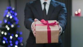 Mensen` s Handen die een Kerstmisgift houden stock footage