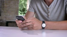 Mensen` s handen die op mobiele telefoon texting, die bij lijst in modern bureau zitten stock videobeelden