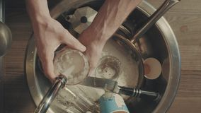 Mensen` s handen die schotels in de keuken na ontbijt wassen stock video