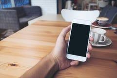 Mensen` s handen die witte mobiele telefoon met het lege zwarte scherm en witte koffiekoppen in moderne zolderkoffie houden Royalty-vrije Stock Fotografie