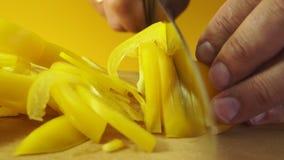 Mensen` s handen die zoete gele groene paprika snijden stock video