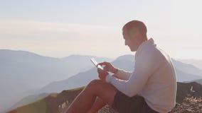 Mensen` s handen wat betreft het scherm van digitale tablet op de achtergrond van bergen stock videobeelden