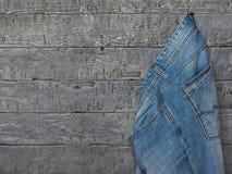 Mensen` s jeans die op de houten muur van ruwe raad hangen Stock Foto's
