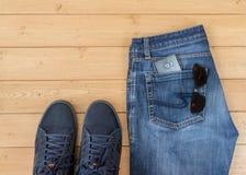 Mensen` s jeans en toebehoren op de houten vloer Stock Fotografie