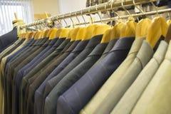 Mensen` s kostuums in een opslag van de mensen` s kleding stock afbeelding