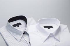 Mensen` s overhemden op een witte achtergrond worden gevouwen die stock foto's