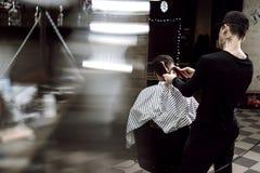 Mensen` s stijl De manierkapper maakt een modieus kapsel voor een zwart-haired mensenzitting in de leunstoel in modieus stock afbeelding