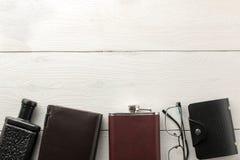 Mensen` s toebehoren Mensen` s stijl adreskaartjehouder, parfum, fles, glazen en beurs op een witte houten achtergrond Vlak leg stock afbeelding