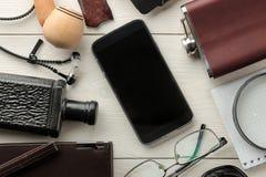 Mensen` s toebehoren Mensen` s stijl Smartphone, band, sleutels, portefeuille, adreskaartjehouder, fles, glazen, pen en notitiebo stock foto's