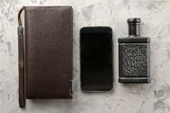 Mensen` s toebehoren Mensen` s stijl Smartphone, portefeuille en parfum op een lichte concrete achtergrond Vlak leg stock foto