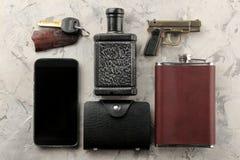 Mensen` s toebehoren Mensen` s stijl Smartphone, portefeuille, fles, sleutels, adreskaartje, en parfum op een lichte concrete ach royalty-vrije stock foto's