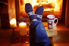 Mensen` s voeten in warme sokken met grote mok hete chocolade en murshmallows dichtbij open haard stock fotografie