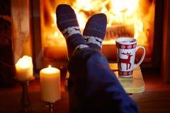Mensen` s voeten in warme sokken met grote mok hete chocolade en murshmallows dichtbij open haard royalty-vrije stock fotografie