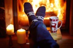 Mensen` s voeten in warme sokken met grote mok hete chocolade en murshmallows dichtbij open haard stock afbeeldingen