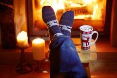 Mensen` s voeten in warme sokken met grote mok hete chocolade en murshmallows dichtbij open haard stock afbeelding