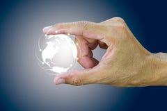 Mensen` s wijsvinger en de bol van de duimholding met verbinding wereldwijd Stock Afbeelding