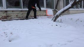 Mensen schone sneeuw met schop dichtbij huismuur in de wintertijd 4K stock videobeelden