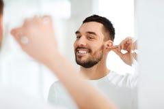 Mensen schoonmakend oor met katoenen zwabber bij badkamers Stock Afbeelding