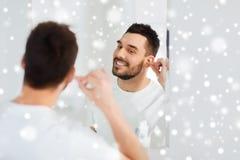 Mensen schoonmakend oor met katoenen zwabber bij badkamers Stock Foto's