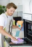 Mensen schoonmakende oven in keuken stock foto